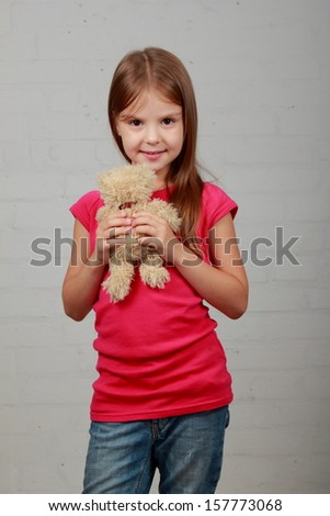 Portrait of an adorable toddler girl hugging a teddy bear