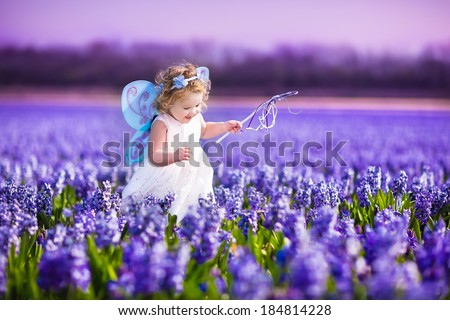 Portrait of an adorable toddler girl in a magic fairy costume and flower crown in her curly hair playing with a wand in a beautiful field of purple hyacinths in Keukenhof, Holland on windy spring day  - stock photo