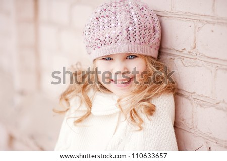 Portrait of an adorable toddler girl wearing fashion knitted clothes, a sweater and hat in pink and white