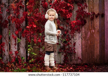 Portrait of an adorable toddler girl wearing fashion knitted clothes at autumn background, near fence with red maple leaves