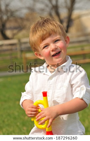 portrait of an adorable toddler playing with a toy trumpet - stock photo
