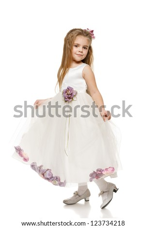 Portrait of an adorable 6 years old girl in princess dress, over white background