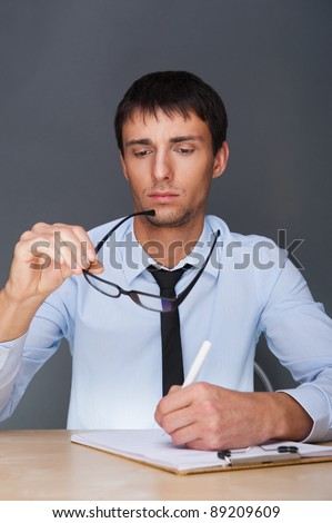 Portrait of an adult business man sitting in the office and signing documents