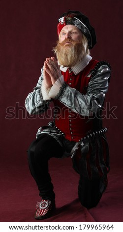Portrait of an adult male in medieval costume with a beard and a mustache standing on one knee, and with her hands clasped in prayer - stock photo