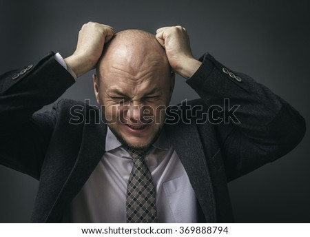 Portrait of an adult man in a business suit on a black background. Regrets wrong doing - stock photo