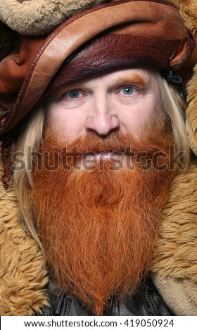 Portrait of an adult man with a red beard and mustache with a teddy bear on a dark background studio - stock photo