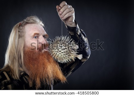 Portrait of an adult man with a red beard and mustache with the globefish on a dark background studio - stock photo