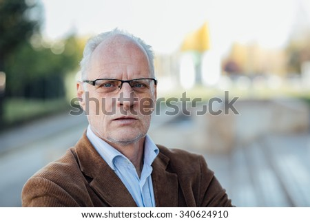portrait of an adult person with gray hair and eyeglasses elegant dressed outside - stock photo