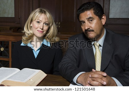 Portrait of an advocate sitting with colleague in courtroom - stock photo