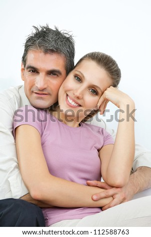 Portrait of an affectionate couple embracing over white background
