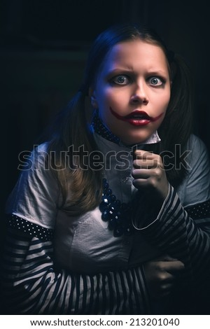 Portrait of an afraid clown teen girl - stock photo