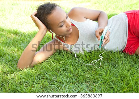 Portrait of an african american black teenager young woman laying on green grass in park, relaxing listening to music using a smartphone mobile, outdoors. Adolescent technology lifestyle exterior.