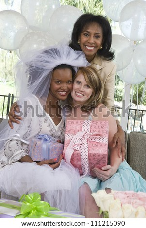 Portrait of an African American bride holding gift with her mother and friend at party