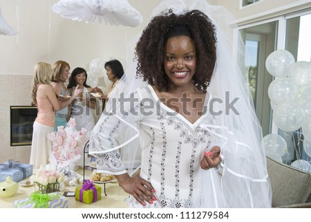 Portrait of an African American bride with friends in the background at party