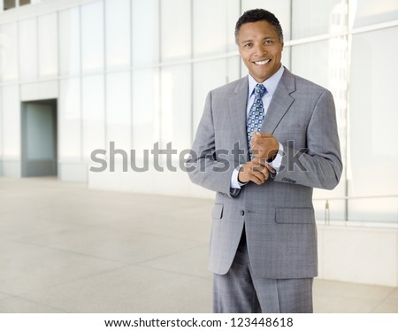 Portrait of an African American businessman wearing a suit standing in an outdoor business environment - stock photo