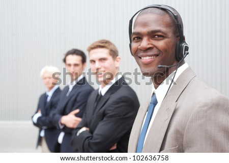 portrait of an African American businessman with coworkers in background