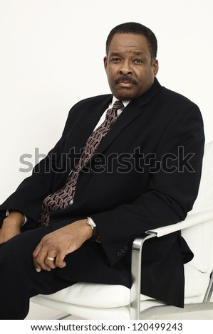 Portrait of an African American confident businessman sitting on chair isolated over white background