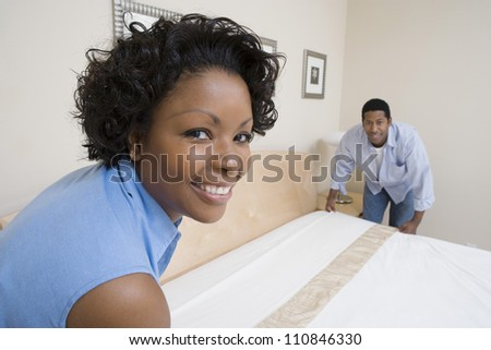Portrait of an African American couple arranging bed at home - stock photo