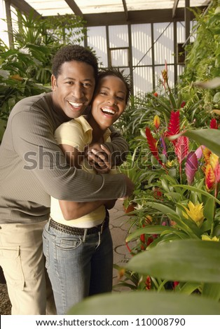 Portrait of an African American couple hugging at botanical garden - stock photo