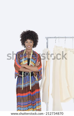 Portrait of an African American female designer with sewing patterns on clothes rack over gray background - stock photo
