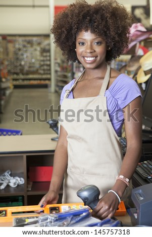 Portrait of an African American female store clerk standing at checkout counter - stock photo