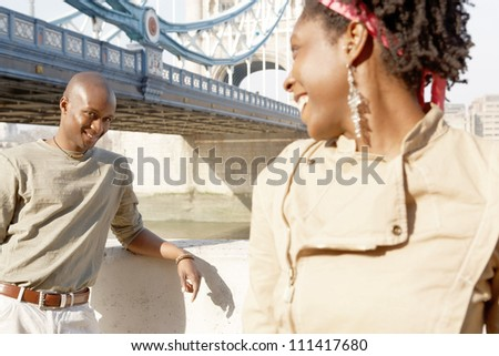 Portrait of an african american man and woman standing by Tower Bridge while sightseeing in London, flirting with each other. - stock photo