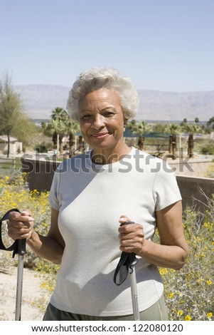 Portrait of an African American senior woman holding trekking pole in park