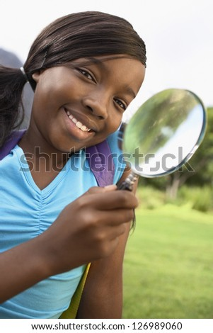 Portrait of an african american teenage girl with magnifying glass - stock photo