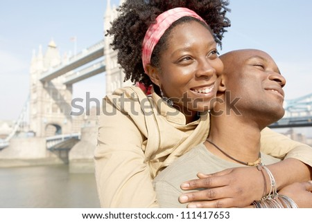 Portrait of an african american tourist couple visiting the Tower of London overlooking the river, being joyful.