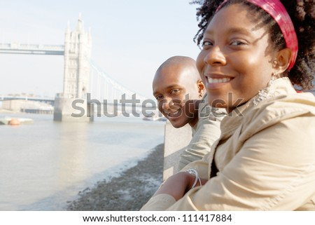 Portrait of an african american tourist couple visiting the Tower of London overlooking the river, smiling. - stock photo