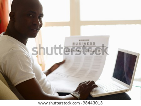 Portrait of an African American with newspaper and laptop