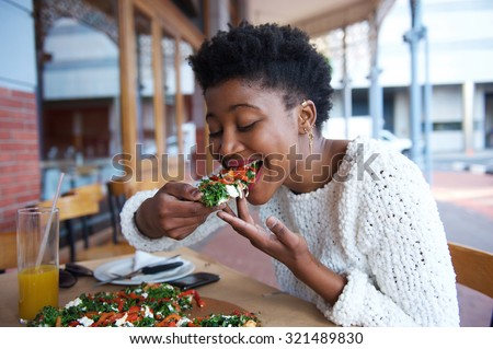 Portrait of an african american woman eating pizza at outdoor restaurant - stock photo