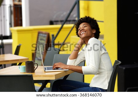 Portrait of an african american woman laughing with laptop at cafe - stock photo