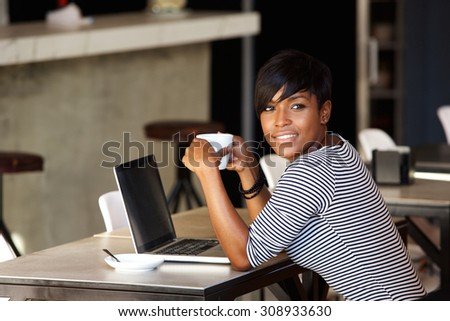 Portrait of an african american woman relaxing at cafe with laptop and coffee - stock photo
