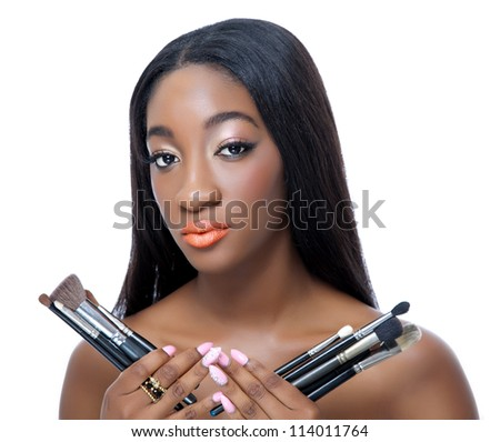 Portrait of an African beauty holding make up brushes - stock photo