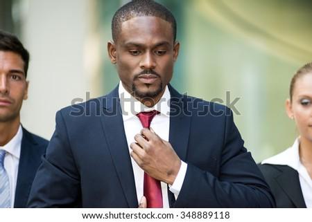 Portrait of an african businessman adjusting his necktie - stock photo