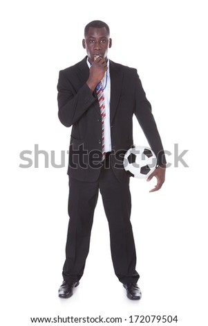 Portrait Of An African Businessman Holding Football Blowing Whistle - stock photo