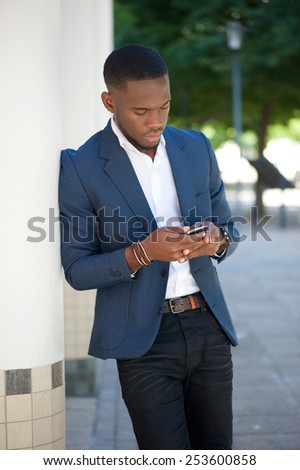 Portrait of an african businessman sending text message on mobile phone - stock photo