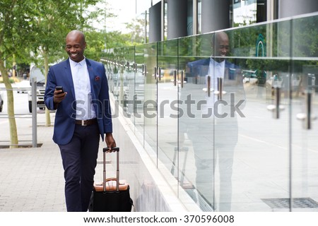 Portrait of an african businessman walking with bag and looking at mobile phone - stock photo