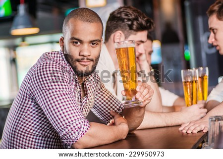 Portrait of an African man with a glass of beer. Three cheerful friends met at the bar and drink a beer while the bartender is standing on the bar. Friends having fun together