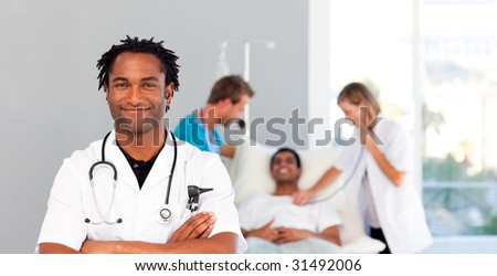 Portrait of an African young doctor with a patient in the background - stock photo