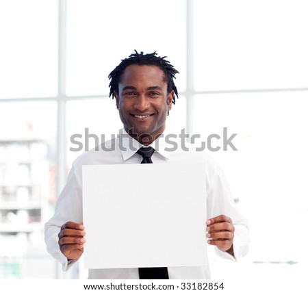 Portrait of an Afro-American businessman holding a white card in office - stock photo