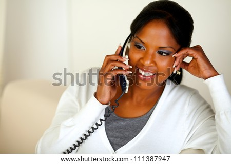 Portrait of an afro-American female conversing on phone while sitting on couch at home. With copyspace