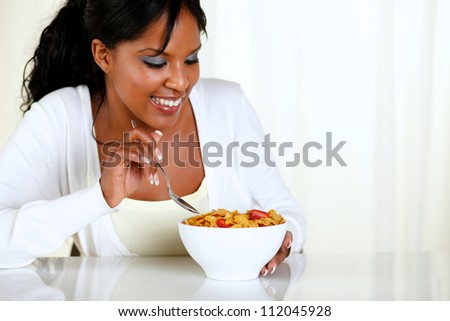 Portrait of an afro-american female eating a bowl of cereals with strawberries at soft colors composition. with copyspace - stock photo