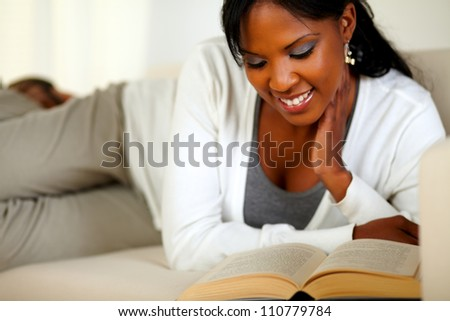 Portrait of an afro-American girl smiling and reading a book while lying on couch at home indoor - stock photo