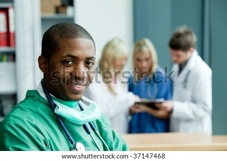 Portrait of an Afro-American surgeon with folded arms smiling at the camera - stock photo