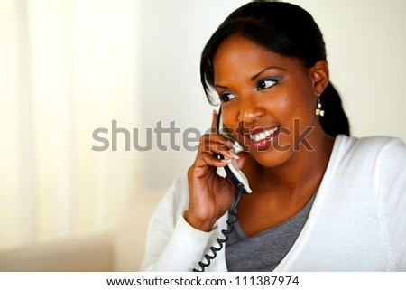 Portrait of an afro-American woman conversing on phone at soft colors composition. With copyspace