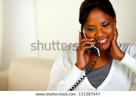 Portrait of an afro-american woman conversing on phone while sitting on couch at home. With copyspace