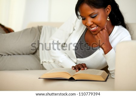 Portrait of an afro-American woman reading a book while lying on couch at home indoor