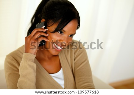Portrait of an afro-American woman speaking on mobile phone at home indoor - stock photo